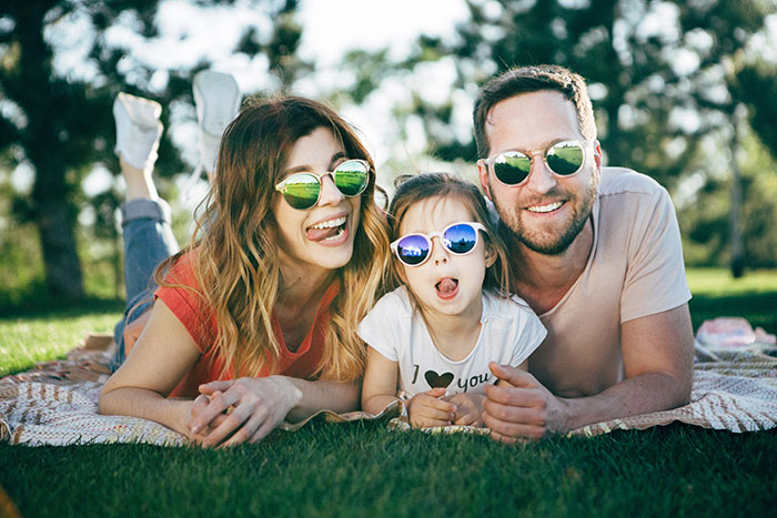 Family laying on blanket outside wearing sunglasses