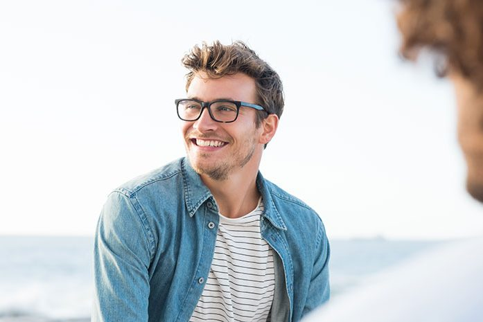 man with glasses smiling outside